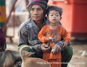 Man and small child with dogs, Cambodia (Photo by Anna Willett) unitedworldschools org